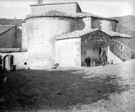 Cellers: Absis i façana sud del monestir de Sant Celdoni i Sant Ermenter de Cellers amb algunes persones al voltant  Cèsar August Torras
